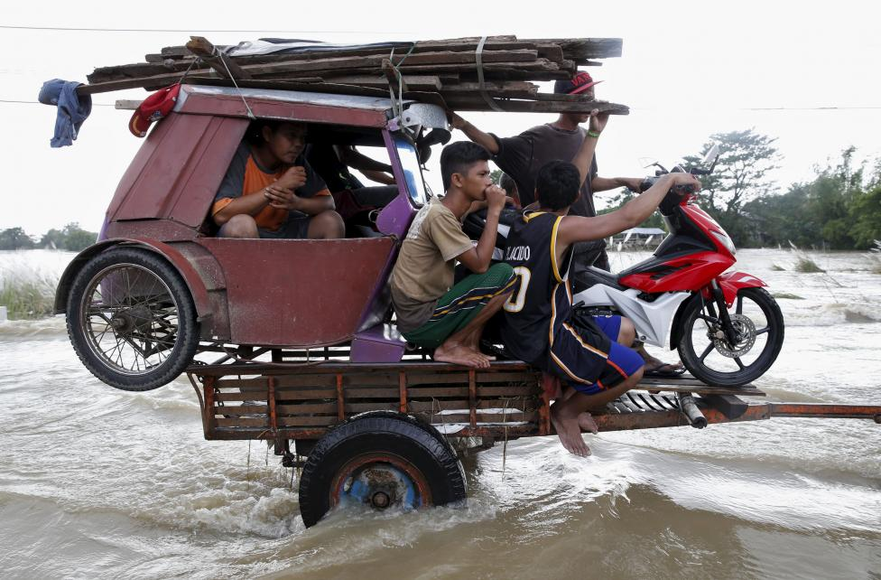 A tricycle and residents are pulled on a farm tractor trailer along a flooded highway in Zaragoza, Nueva Ecija