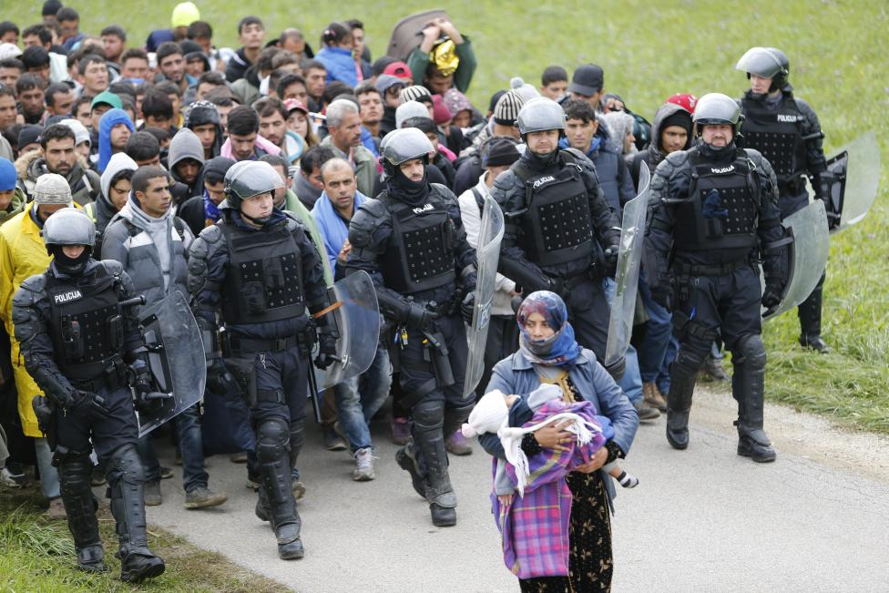 Police officers escort migrants as they make their way on foot after crossing the Croatian-Slovenian border in Rigonce