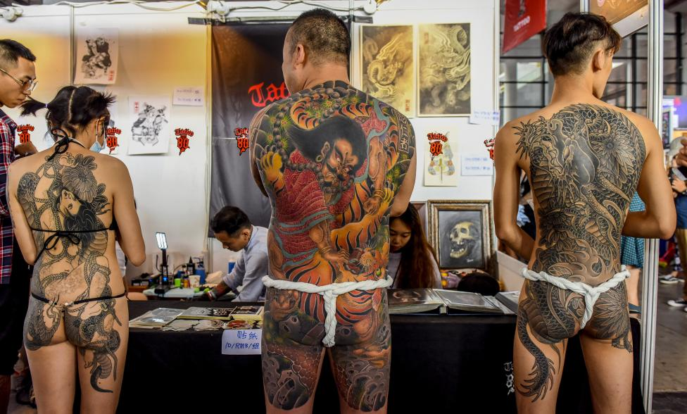 Contestants of a tattoo competition pose for photographs at the China TATTOO convention in Nanning