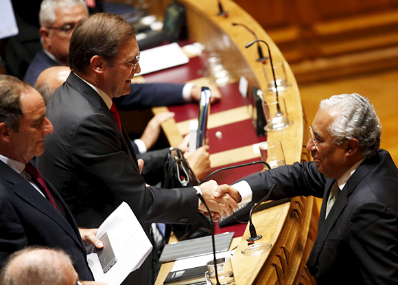 Portugal's Prime Minister Pedro Passos Coelho shakes hands with Socialist party leader Antonio Costa at the end of a debate on government programmes at the parliament in Lisbon, Portugal